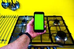 有绿色屏幕的电话有厨房的背景 库存图片