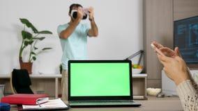 有绿色屏幕的膝上型计算机在与一名美丽的白肤金发的自由职业者妇女的桌上在钛旁边 股票录像