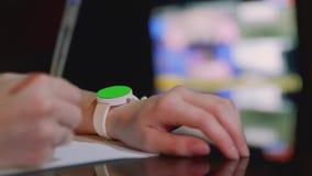 有绿色屏幕的被聚焦的白色手表在女孩` s左手和在女孩` s右手的defocused笔 影视素材