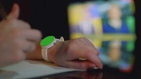 有绿色屏幕的被聚焦的白色手表在女孩` s左手和在女孩` s右手的defocused笔 股票视频