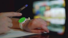 有绿色屏幕的被聚焦的白色手表在女孩` s左手和在女孩` s右手的defocused笔 股票录像