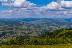 有绿色山脉和小屋的全景一个谷的在多云天空下 库存照片