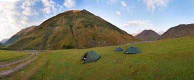 有绿色旅游帐篷的五颜六色的夏天全景在山下的谷在天空蔚蓝下 狂放美丽的山 免版税图库摄影