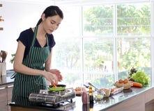 有绿色条纹围裙厨师的年轻美丽的亚裔妇女平底锅的 免版税库存图片