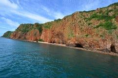 有绿色树的长的岩石海岛在蓝色海 库存照片
