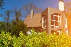 有绿色树篱的土气房子 晴朗的天气 库存照片