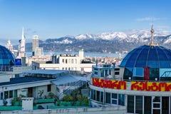 有绿色植物的餐馆俯视积雪的山的现代高层建筑物屋顶的  免版税库存照片