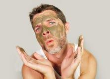 有绿色海草面部面具的滑稽的人在他的摆在镜子前面的面孔嘲笑在他自己使用护肤秀丽刺 免版税库存照片