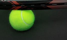 有绿色球的黑和红色球拍 库存图片