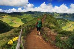 有绿色背包的妇女走在足迹的导致绿色和蓝色湖,圣地米格尔海岛 免版税库存图片