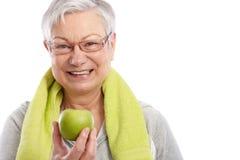 有绿色苹果微笑的健康老妇人 库存照片