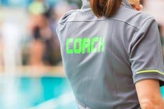 有绿色词的教练书面o一件教练` s灰色衬衣 免版税库存照片