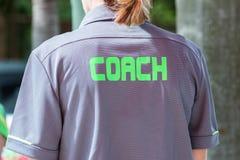 有绿色词的教练书面o一件教练` s灰色衬衣 免版税库存图片