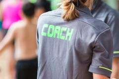 有绿色词的教练书面o一件教练` s灰色衬衣 库存照片