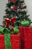 有绿色鞋带和圣诞树的红色礼物盒在背景中 库存图片