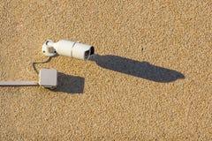 有缆绳的一台白色街道摄影机在一个混凝土墙上垂悬 免版税库存图片