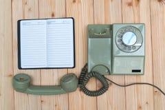有缆绳的减速火箭的转台式电话和白色空的纸或者noteb 免版税库存照片