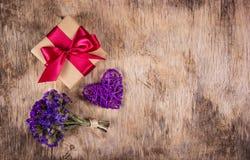 有缎丝带、柳条心脏和花的礼物盒在老木背景 复制空间 免版税库存图片