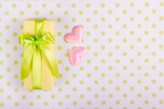 有缎丝带的黄色礼物盒和在圆点背景的两桃红色心脏 库存照片