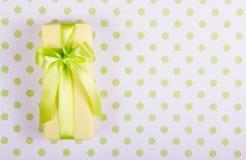 有缎丝带的黄色礼物盒在圆点背景 免版税图库摄影