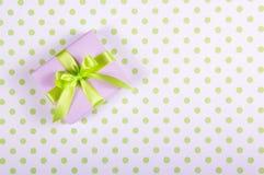 有缎弓的淡紫色礼物盒在圆点背景 库存图片