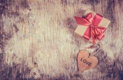 有缎弓的礼物盒和在老木背景的木心脏 减速火箭定调子 免版税库存照片