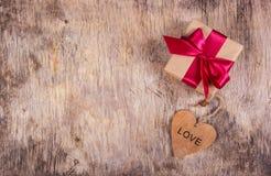有缎弓的礼物盒和在老木背景的木心脏 复制空间 免版税图库摄影