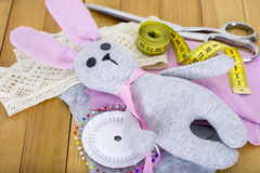 有缝合的辅助部件的手工制造兔宝宝玩具在木背景 免版税库存照片