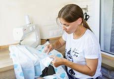有缝纫机的少妇缝合的衣裳 免版税库存照片