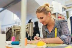 有缝纫机的少妇 免版税库存照片