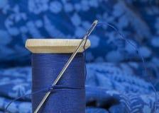 有缝纫针的缝合针线短管轴,在蓝色织品backgroun 免版税库存图片
