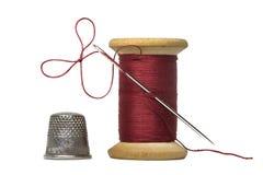 有缝纫针的缝合针线被隔绝的短管轴和顶针  免版税库存图片