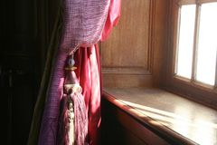 有缨子的由靠窗座位,法国典雅的帷幕 免版税库存照片