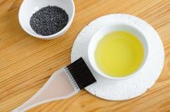 有罂粟油和罂粟种子的小陶瓷碗 自创化妆用品和自然护肤的成份 免版税图库摄影