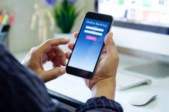 有网上银行应用电话的人在书桌工作区在办公室 免版税图库摄影