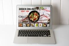 有网上食物交付的app计算机在屏幕上 浓缩的生活方式 库存照片