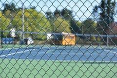 有网球场和学校班车的篱芭 库存图片