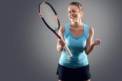 有网球拍庆祝的运动妇女 免版税库存图片