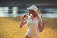 有网球拍的女运动员在河 网球成套装备的时尚妇女在夏天风景 盖帽的妇女在晴朗 免版税库存图片