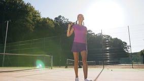 有网球拍的逗人喜爱的微笑的女孩走在网球场的 影视素材