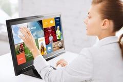 有网页的妇女在触摸屏幕在办公室 免版税库存图片