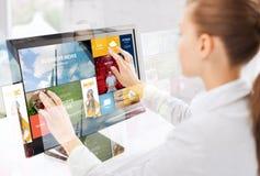 有网页的妇女在触摸屏幕在办公室 库存照片