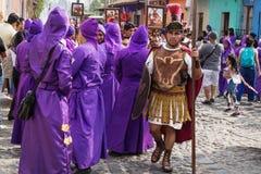 有罗马战士服装的人走沿紫色着长袍的人的在圣Bartolome在1a的de Becerra队伍  库存照片