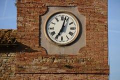 有罗马数字的塔时钟在砖墙前面 免版税库存照片