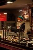 有羊毛帽子服务的妇女加香料面包在圣诞节市场上 免版税库存图片