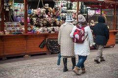 有羊毛帽子的人走在软的玩具前面的圣诞节市场上的购物 免版税图库摄影