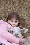 有羊羔的女孩在干草 免版税库存照片