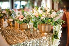 有美丽和嫩白玫瑰的金黄罐 库存照片