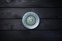 有美丽的五颜六色的装饰品的东方陶瓷板材 顶视图黑暗的木背景 库存照片