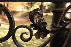 有美丽的伪造的卷毛和形状特写镜头的金属篱芭 在篱芭后是公园,路灯柱,桥梁 图库摄影